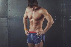 Portrait of fit athletic muscular shirtless young man looking down photo