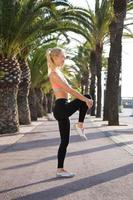 Fit woman with slender figure doing warm up exercising outdoors
