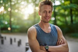 homem saudável e em forma no parque sorri para a câmera