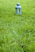 Blue Lantern, with burning candle inside, on green grass photo