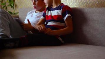 due ragazzi giocano su un piatto bianco seduto sul divano
