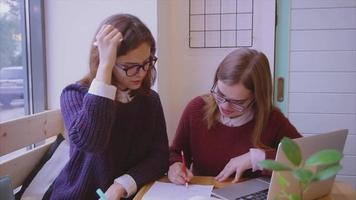 Female college students studies in the cafe two girls friends learning together video