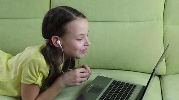 Beautiful little girl lying on the couch and watching movie on laptop