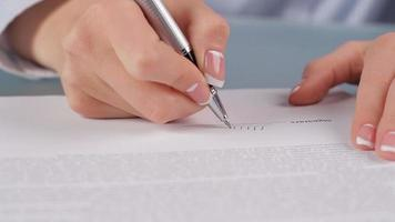 Woman signing  contract.