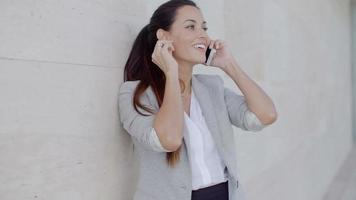 Woman leaning on a wall chatting on a mobile video