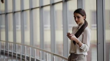 Woman using mobile phone at the office video