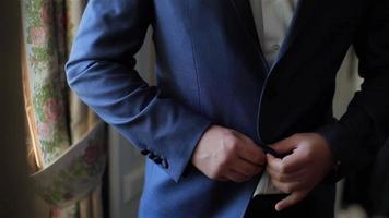 abotoar uma jaqueta com as mãos fecham. elegante sem rosto homem de terno fecha os botões e endireita a jaqueta se preparando para sair. dedos nervosos, preparem-se antes do encontro ou encontro com estilo de moda e ajuste de peso