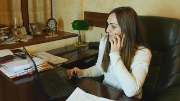 Hermosa mujer de negocios trabajando en un portátil y hablando por teléfono en la oficina video