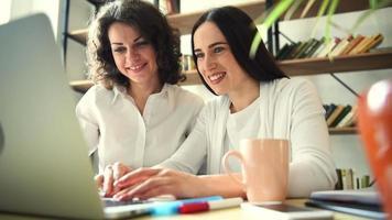 dos hermosas chicas con laptop felices de lo que ven en la pantalla