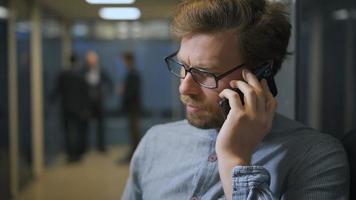 employé de bureau dans le hall en parlant sur son smartphone