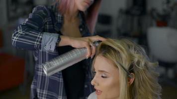 Mujer con maquillaje en un salón de belleza. peluquero profesional hace peinado para rubias video