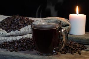 Cup of Hot black coffee with coffee beans and candle photo