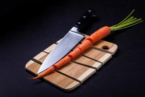 Knife with carrot and wooden cutting board photo