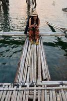 Thai women play mobile at Antique bamboo bridge