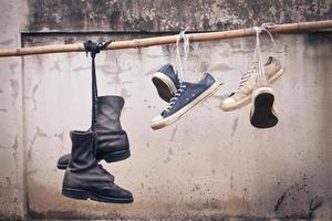 pair of old sneakers and old boot hang