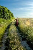 Hermosa mujer rubia en un camino hacia un campo de trigo