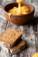 slices of brown bread and honey in a clay bowl photo