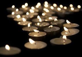 varias velas de té encendidas en la oscuridad foto