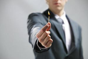 Business man hand holding a burning match