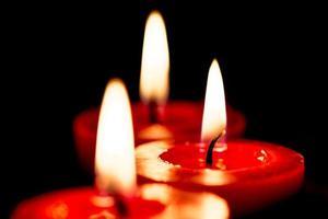 Closeup of burning candles on black background photo