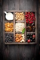 Granola, berries, nuts, dried fruit and milk. Top view. horizontal