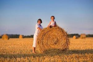 Brother and baby sister playing in field of hay bales