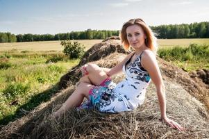 Young blond woman sits on hay