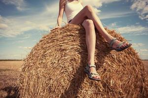 Girl sitting outdoors on haystack