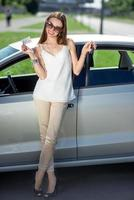 Young woman with key and license near the car