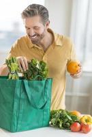 Man Unpacking Bag Of Groceries photo