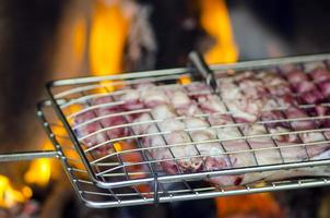 Grill with meat for barbecue fire in background photo