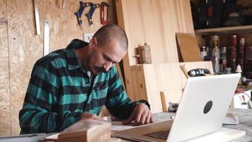 ousado com bigode jovem carpinteiro artesão faz desenho com laptop em sua oficina de madeira video
