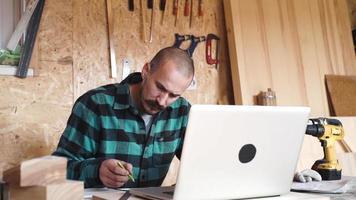 ousado com bigode jovem carpinteiro artesão faz desenho com laptop em sua oficina de madeira