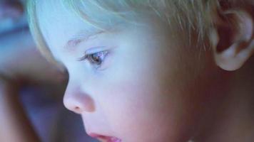 menino deitado embaixo do cobertor assistindo desenhos animados no touchpad closeup video