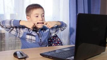 niño de 8 años charla con sus amigos en redes sociales, mucha risa y diversión