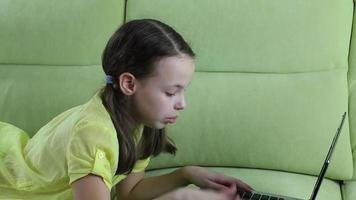 hermosa niña hablando y escribiendo en la computadora portátil