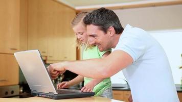figlia che utilizza un laptop mentre il padre sta guardando video