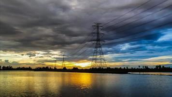 Poste de eletricidade de alta tensão ao pôr do sol.