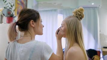 transformación. En el moderno salón de belleza, un maquillador profesional prepara la imagen de una atractiva rubia.