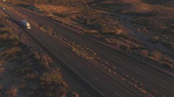 Antenne: volant au-dessus d'un camion semi-remorque transportant des marchandises sur une autoroute très fréquentée