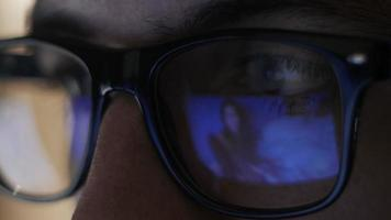 man watching erotic content on internet reflection on glasses