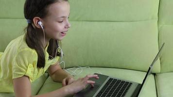 Emotional little girl talking on Skype at laptop