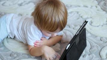 criança olha desenhos animados no tablet pc no chão