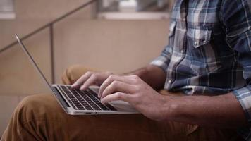 Mann sitzt auf Stufen und arbeitet am Laptop