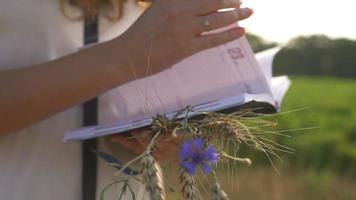 Female hands with pen writing on notebook on grass outside video