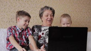 children and grandmother with laptop video