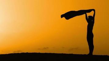 silueta bailando en una playa al atardecer