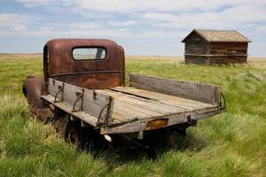 Rusty old pickup truck and shed in a field
