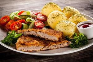 Fried pork chops, boiled potatoes and vegetables on wooden background