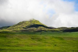 Vista de las colinas brumosas de Islandia contra el fondo de nubes humeantes